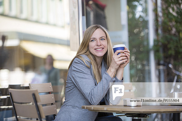 Lächelnde junge Frauen sitzen im Straßencafé mit Kaffee zum Mitnehmen