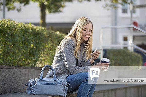 Lächelnde junge Frauen sitzen auf Stufen mit Kaffee zum Mitnehmen mit dem Smartphone