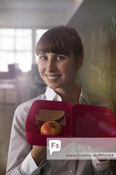 Lächelnde Frau mit Lunchpaket