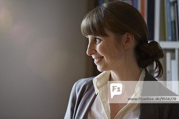 Lächelnde Frau vor dem Bücherregal