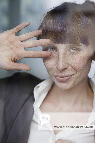Porträt einer lächelnden Frau hinter Glasscheibe