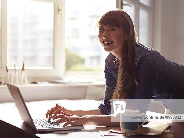 Porträt einer lächelnden Frau am Schreibtisch mit Laptop