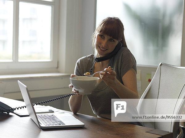 Lächelnde Frau mit Laptop am Schreibtisch am Telefon beim Essen aus der Schüssel