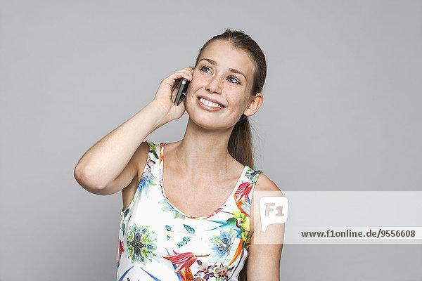 Lächelnde junge Frau beim Telefonieren mit Smartphone vor grauem Hintergrund