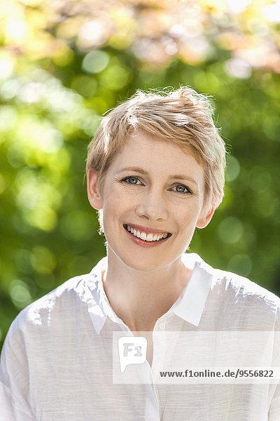 Porträt einer lächelnden Frau mit kurzen blonden Haaren