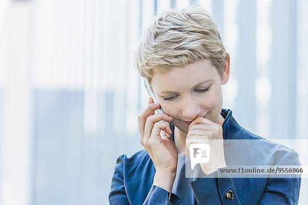 Porträt einer blonden Frau beim Telefonieren mit dem Smartphone nach unten blickend