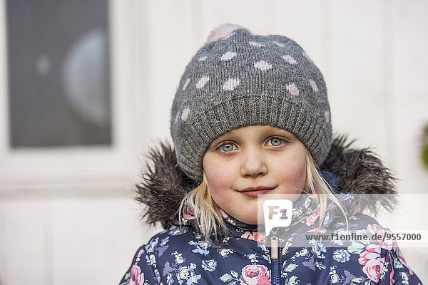 Portrait of little girl wearing wool cap and winter jacket
