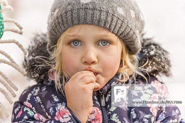 Portrait of little girl wearing wool cap and winter jacket
