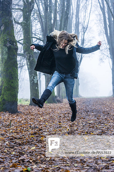 Woman jumping into the air on a forest track