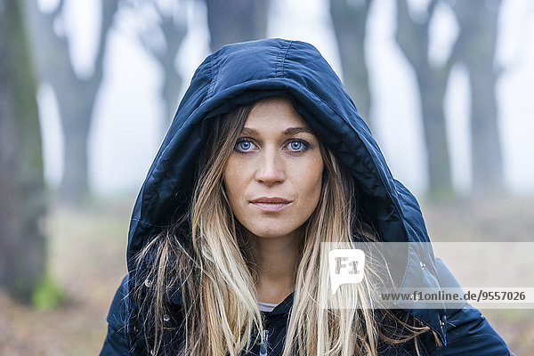 Portrait of serious looking blond woman with blue hood