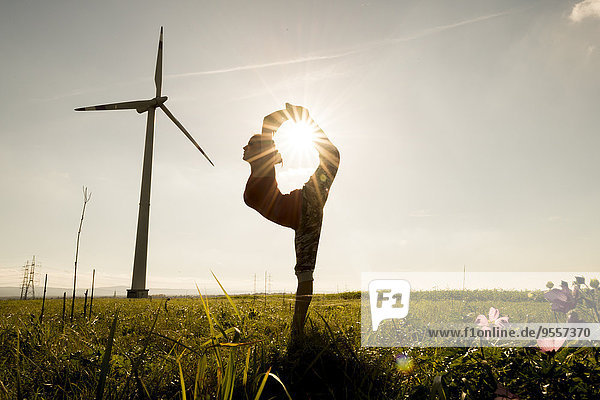 Silhouette der Frau auf der Wiese beim Turnen an der Windkraftanlage