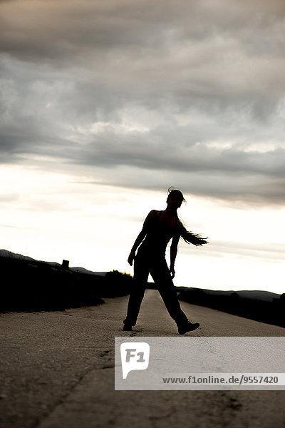 Silhouette einer jungen  sportlichen Frau  die sich in der Dämmerung auf einer leeren Straße bewegt.