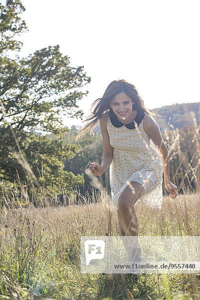 Junge Frau im Sommerkleid entspannt in der Natur