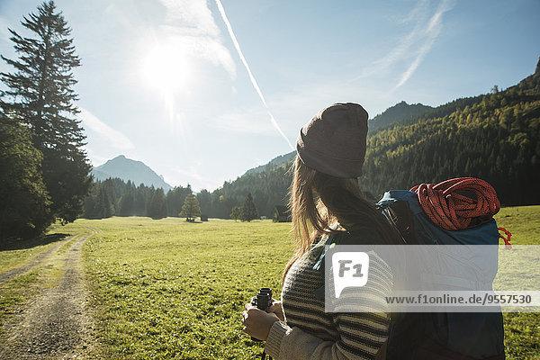 Österreich  Tirol  Tannheimer Tal  junge Wanderin mit Fernglas und Rucksackbeobachtungslandschaft