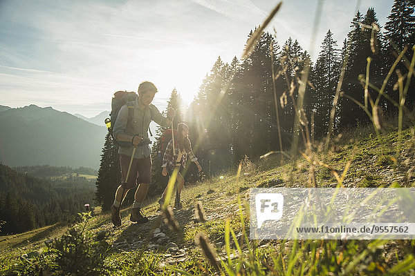 Österreich  Tirol  Tannheimer Tal  junges Paar beim Sonnenwandern auf der Alm
