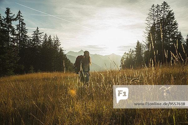 Österreich  Tirol  Tannheimer Tal  junge Frau im Sonnenlicht stehend auf der Alm