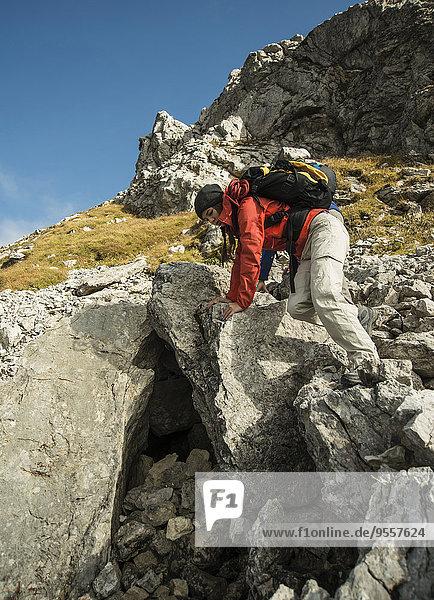 Austria  Tyrol  Tannheimer Tal  young woman climbing on rocks