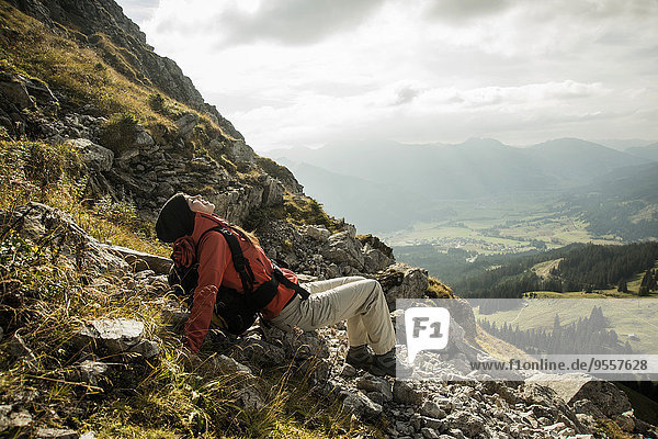 Austria  Tyrol  Tannheimer Tal  young female hiker having a rest in mountains