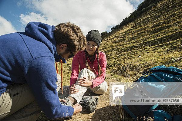 Österreich  Tirol  Tannheimer Tal  junger Mann betreut verletzte Frau auf Wanderung