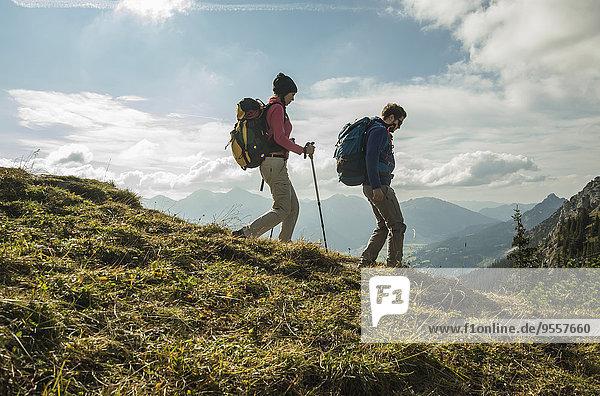 Austria  Tyrol  Tannheimer Tal  young couple hiking on alpine meadow