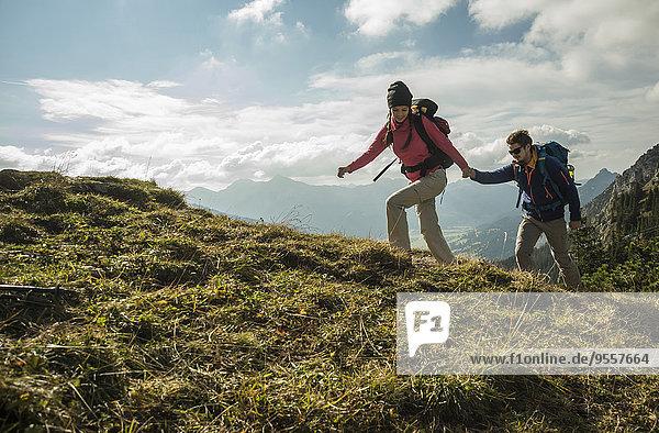 Österreich  Tirol  Tannheimer Tal  junges Paar wandert Hand in Hand auf der Alm