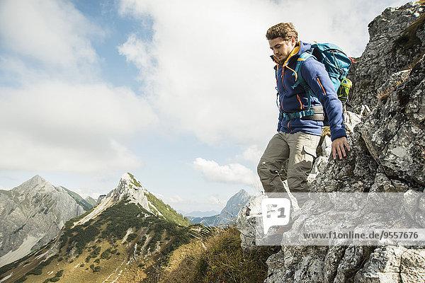 Österreich  Tirol  Tannheimer Tal  junger Mann beim Wandern auf Felsen