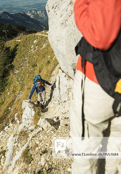 Österreich  Tirol  Tannheimer Tal  junges Paar beim Wandern auf Felsen