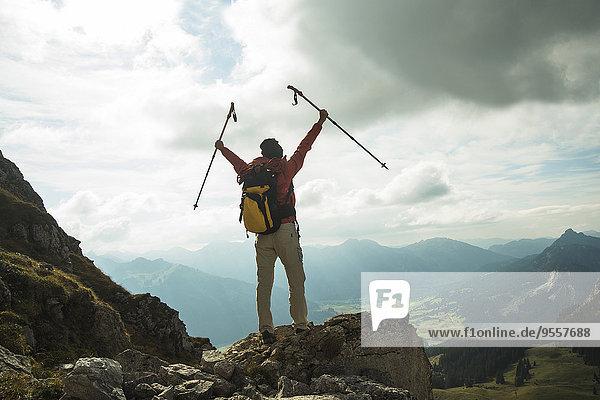Österreich  Tirol  Tannheimer Tal  junge Frau mit Wanderstöcken jubelnd auf dem Berggipfel