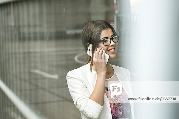 Smiling young businesswoman telephoning with smartphone
