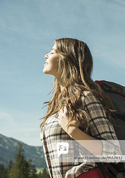 Österreich  Tirol  Tannheimer Tal  junge Frau auf Wanderung bei Sonnenschein