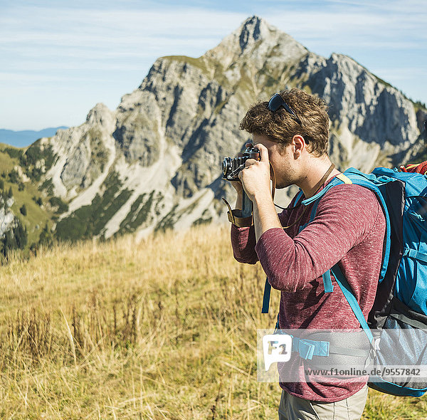 Österreich  Tirol  Tannheimer Tal  junger Mann beim Fotografieren auf Almen