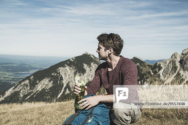 Austria,  Tyrol,  Tannheimer Tal,  young man with backpack and drinking bottle on alpine meadow