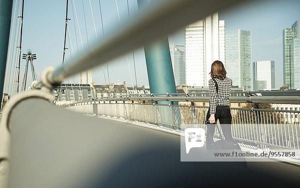 Deutschland  Frankfurt  junge Unternehmerin auf der Brücke