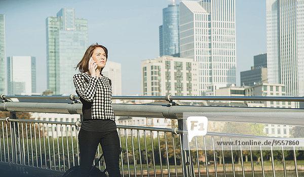 Deutschland  Frankfurt  junge Geschäftsfrau auf Brücke am Handy