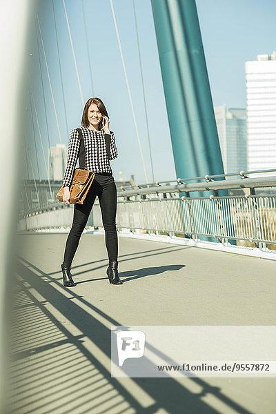 Deutschland  Frankfurt  junge Geschäftsfrau auf Brücke stehend mit Handy