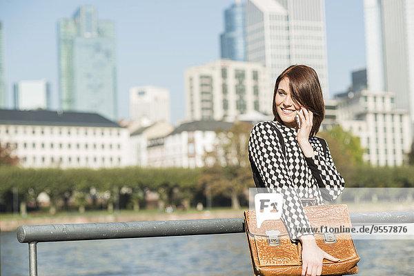 Deutschland  Frankfurt  junge Geschäftsfrau am Flussufer am Handy