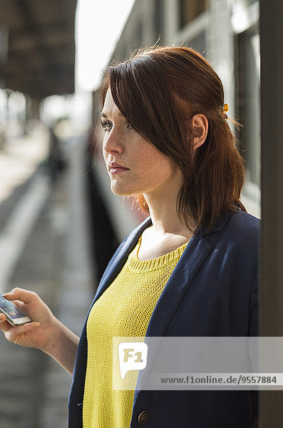 Young woman with cell phone at train station