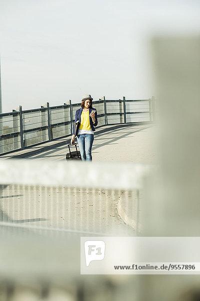 Junge Frau mit Gepäck im Parkhaus