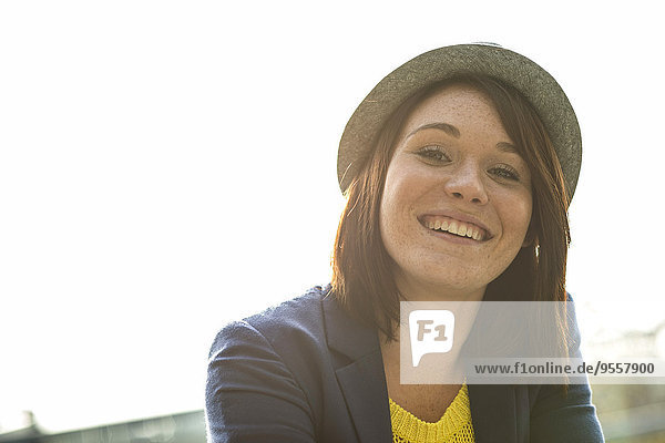 Portrait of smiling young woman wearing hat