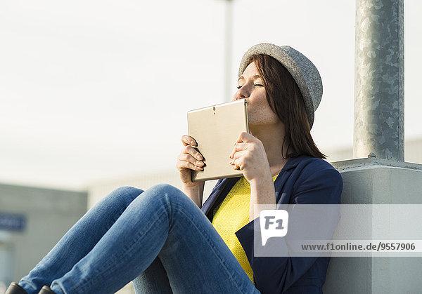 Junge Frau küsst digitales Tablett