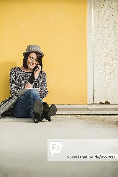 Junge Frau auf dem Boden sitzend mit Notebook und Handy