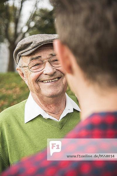 Senior man smiling at adult grandson