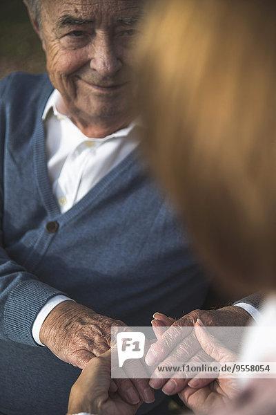 Tochter hält die Hand eines älteren Mannes