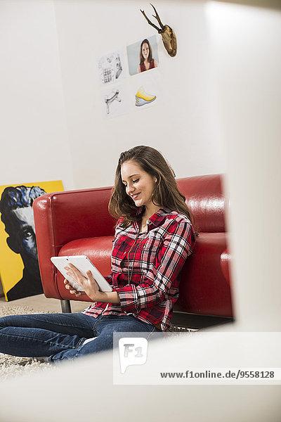 Lächelnde junge Frau mit digitalem Tablett zu Hause