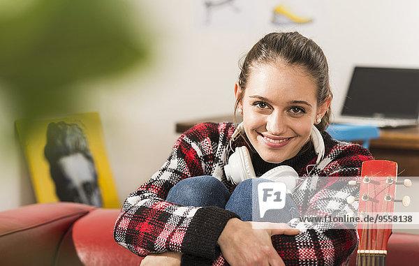 Porträt der lächelnden jungen Frau mit Kopfhörer zu Hause