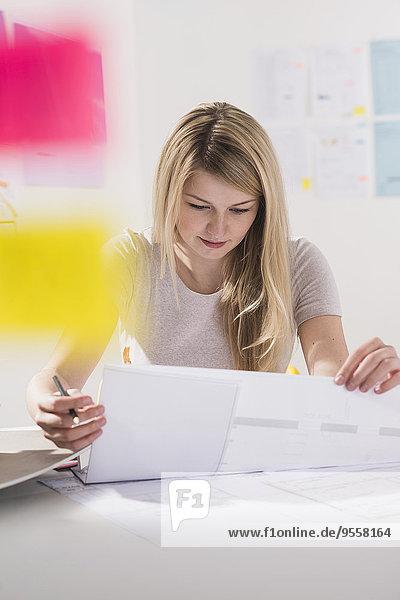 Junge Frau am Schreibtisch beim Betrachten von Dokumenten