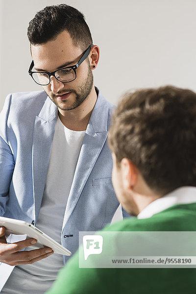 Zwei junge Geschäftsleute mit digitalem Tablett