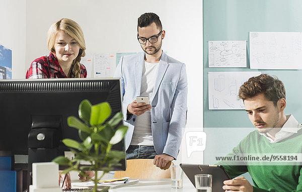 Drei junge Leute im Büro mit Computermonitor