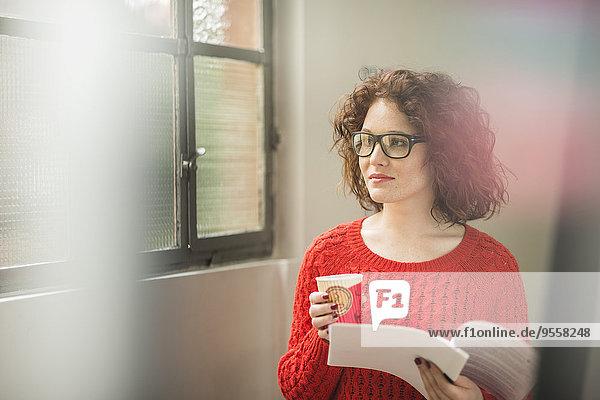 Junge Frau mit Dokument und Kaffee am Fenster