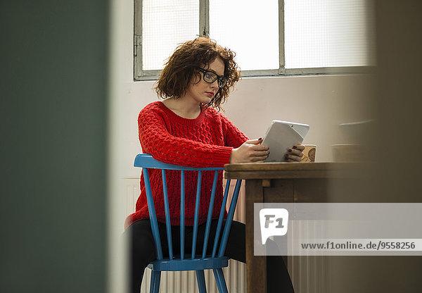 Junge Frau mit digitalem Tablett am Tisch sitzend